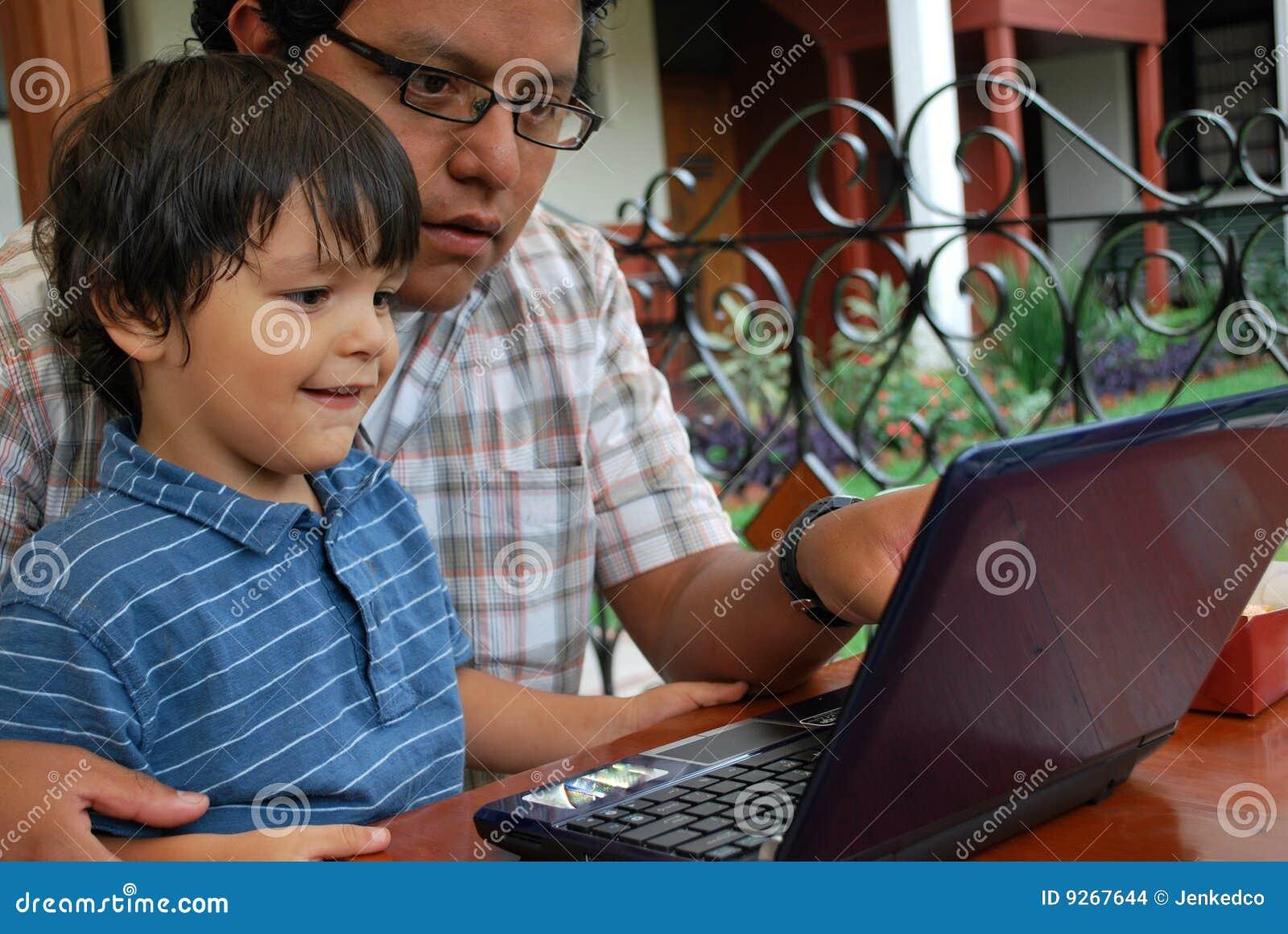 Padre e hijo hispánicos en la computadora portátil