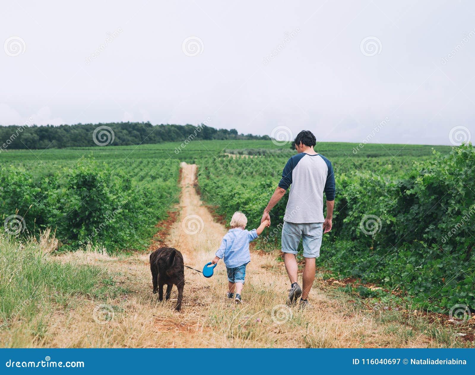 Padre e hijo que caminan con el perro en la naturaleza, al aire libre
