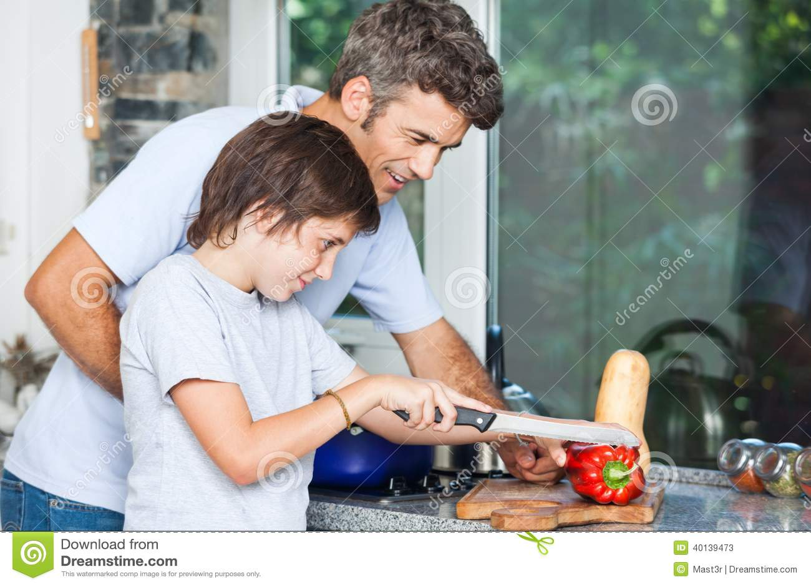 Padre e hijo que cocinan la cocina casera cortando imagen for La cocina casera