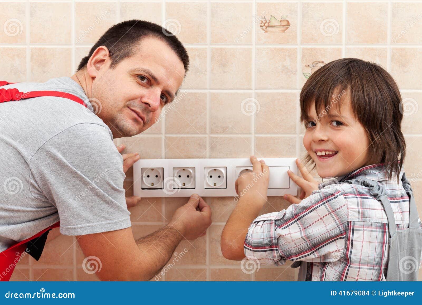 Padre e hijo que instalan los accesorios eléctricos de la pared