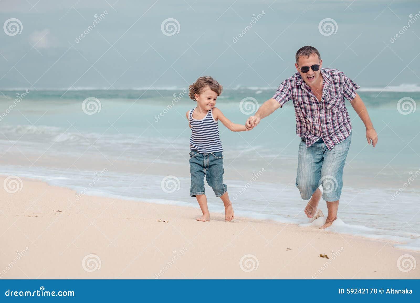 Padre e hijo que juegan en la playa en el tiempo del día