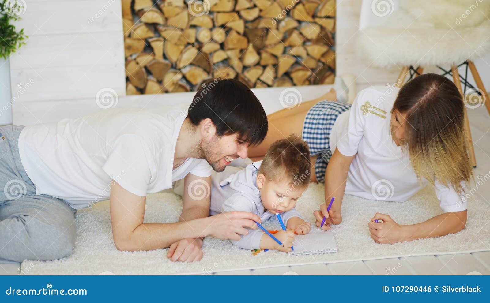Padre e madre che aiuta la loro immagine di tiraggio del bambino nel loro salone