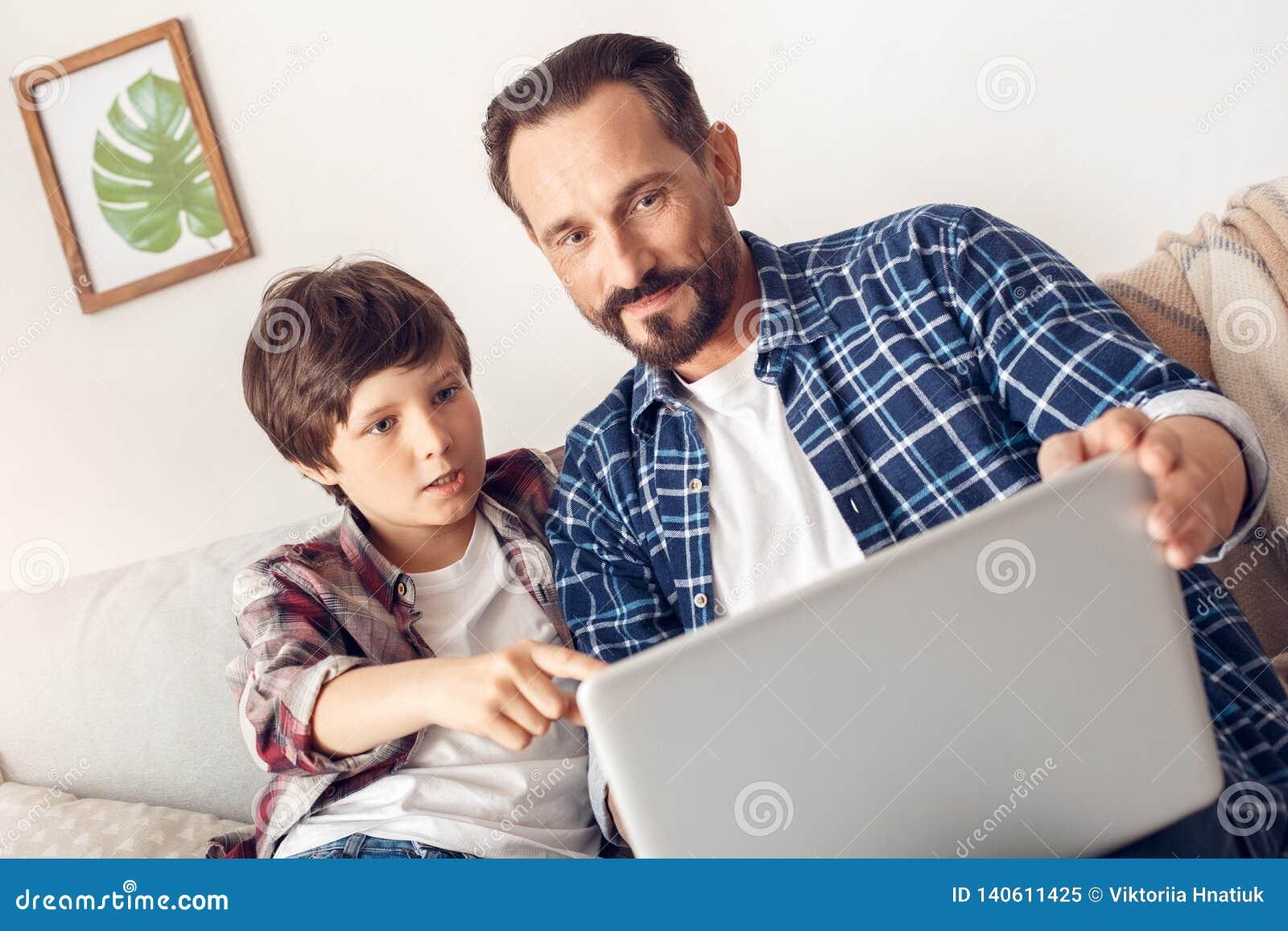 Padre e poco figlio a casa che si siedono sul film di sorveglianza del sofà sul computer portatile che esamina schermo colpito