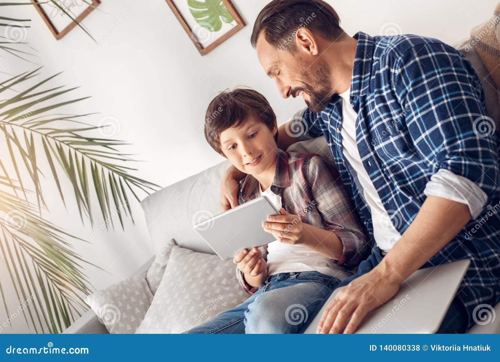 Padre e poco figlio a casa che si siedono sul papà del sofà con il computer portatile che abbraccia ragazzo che gioca compressa d
