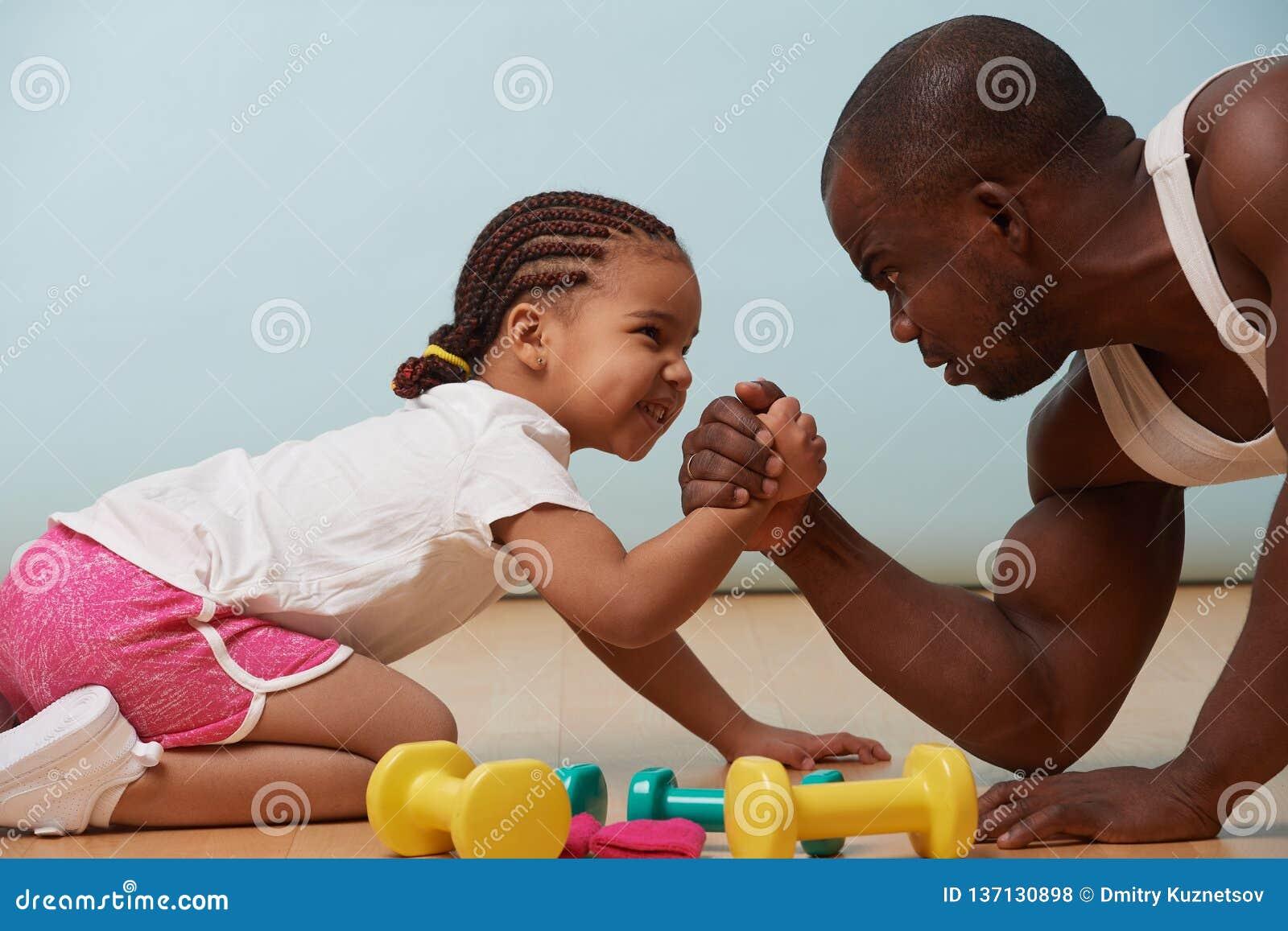 Padre ed il suo piccolo braccio di ferro della figlia sul pavimento a casa