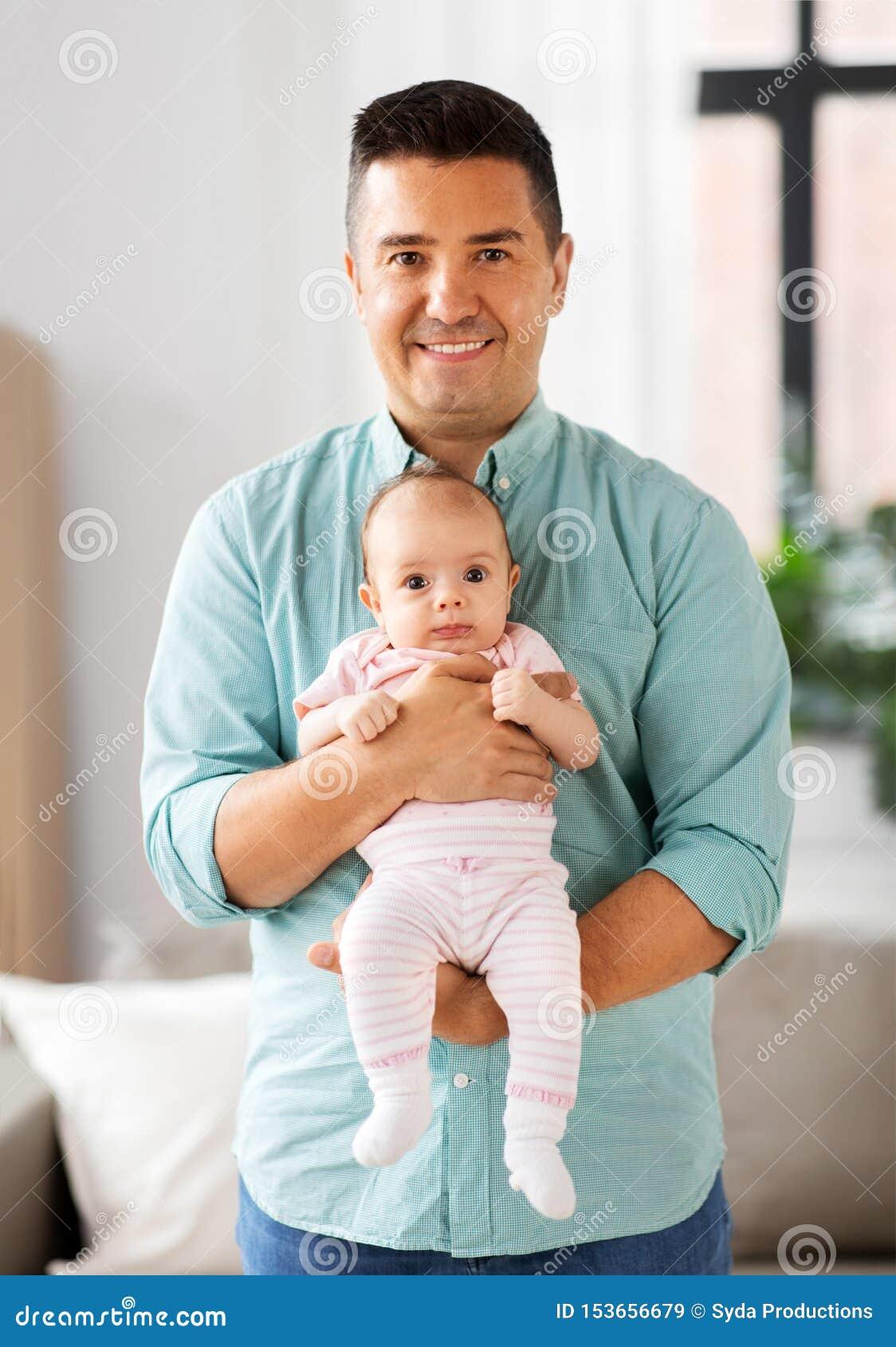 Padre envejecido medio con la hija del bebé en casa