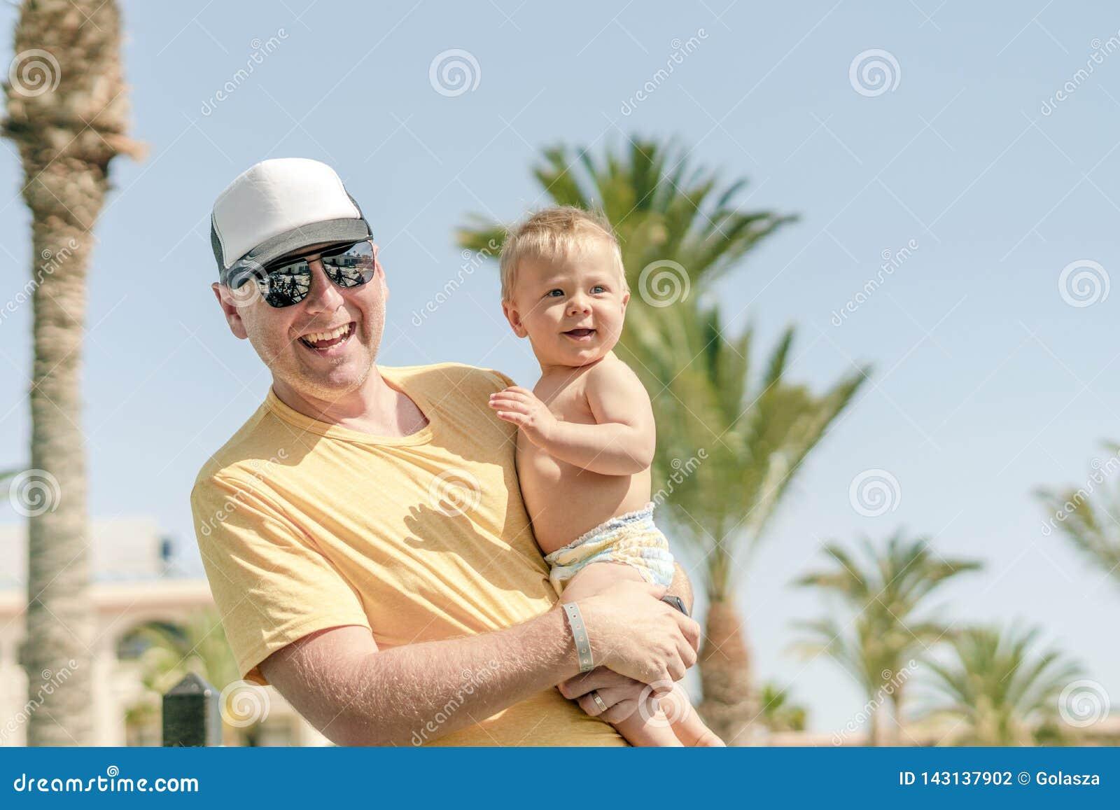 Padre felice che tiene figlio allegro durante la vacanza tropicale