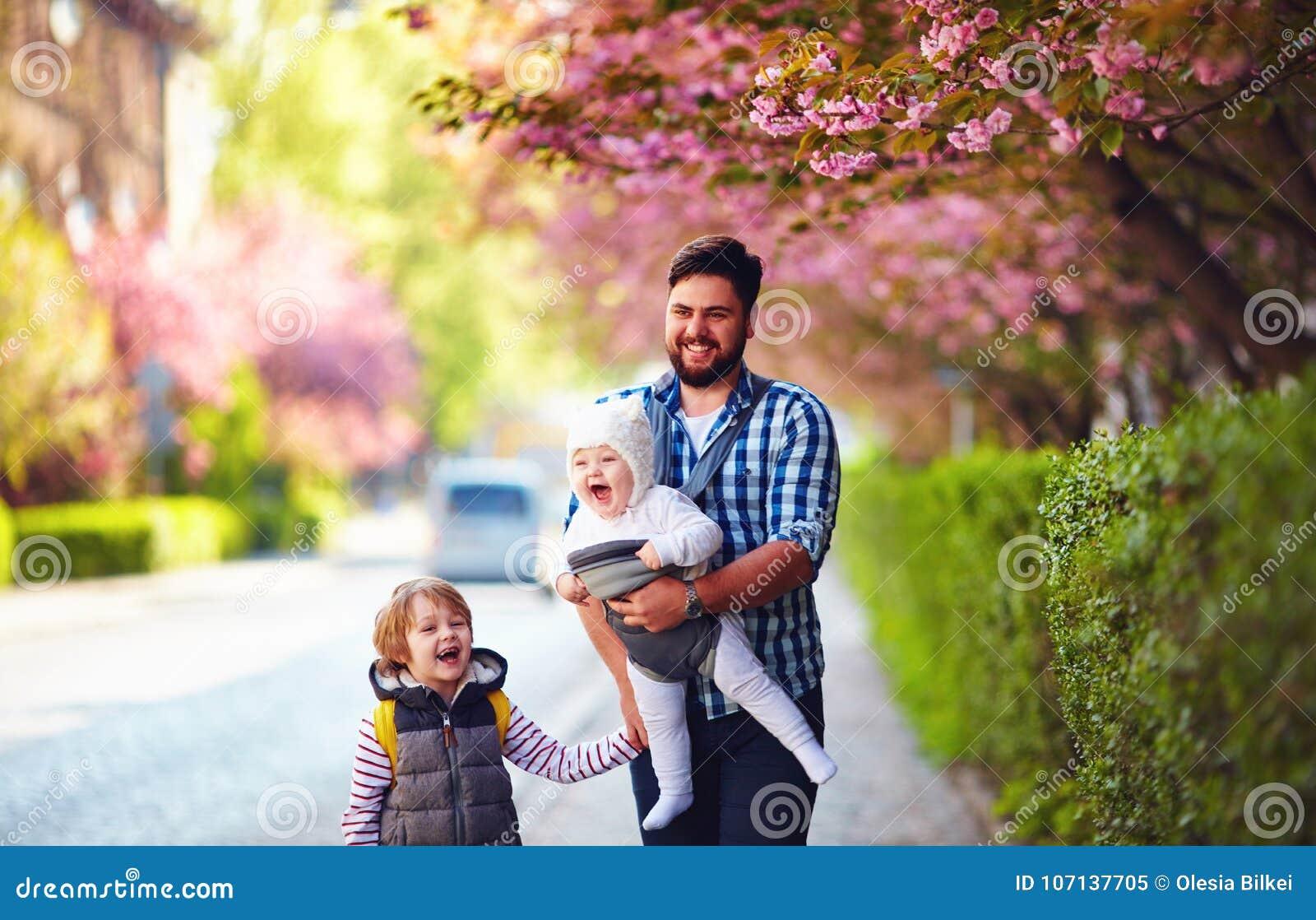 Padre feliz con los niños en el paseo en ciudad de la primavera, portador de bebé, licencia paternal
