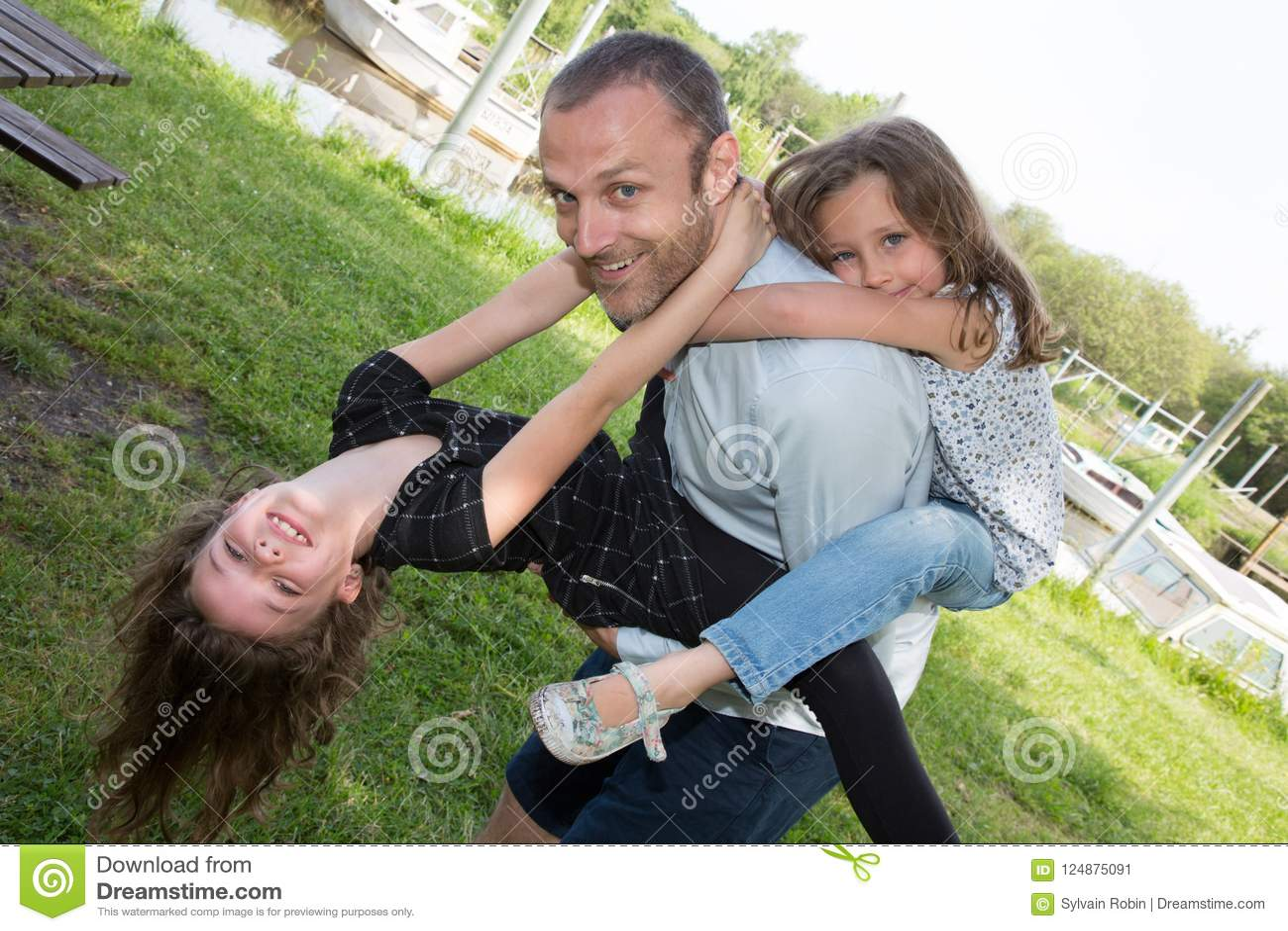 Padre feliz del hombre del concepto de la paternidad de la paternidad de la familia e hija de dos niñas en el transporte por ferr