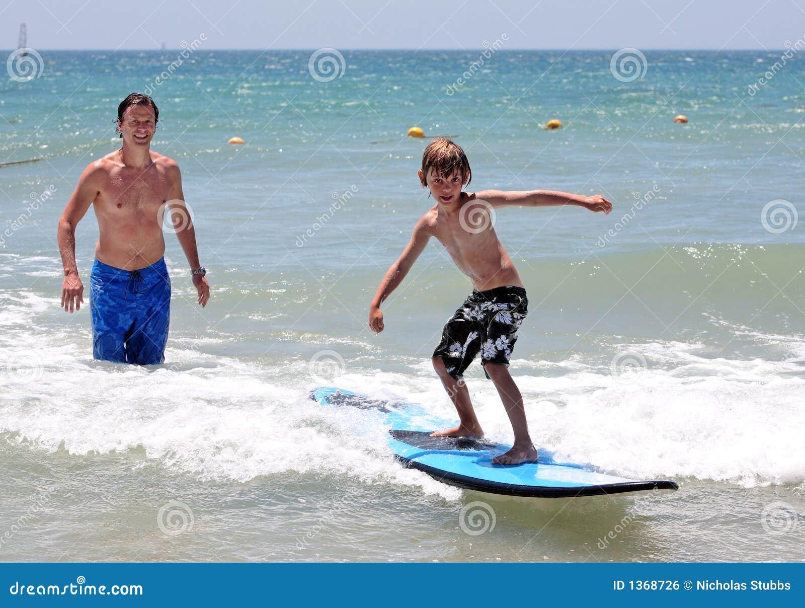Padre feliz que enseña a su hijo joven a practicar surf