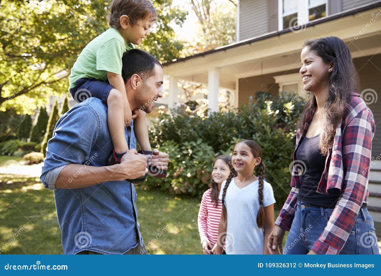Padre Gives Son Ride sulle spalle come Camera di permesso di famiglia