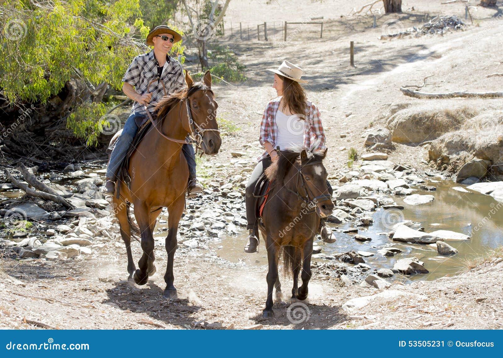 Padre joven como instructor del caballo de la hija adolescente joven que monta el sombrero de la vaquera del pequeño potro que ll