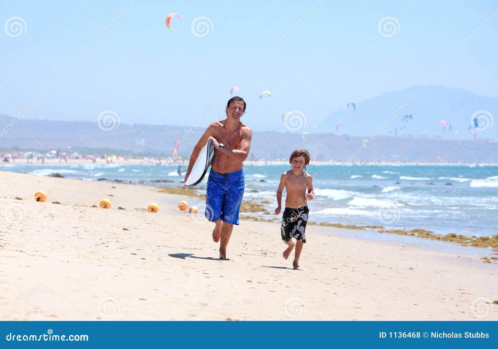 Padre joven e hijo que se ejecutan a lo largo de la playa con la tabla hawaiana