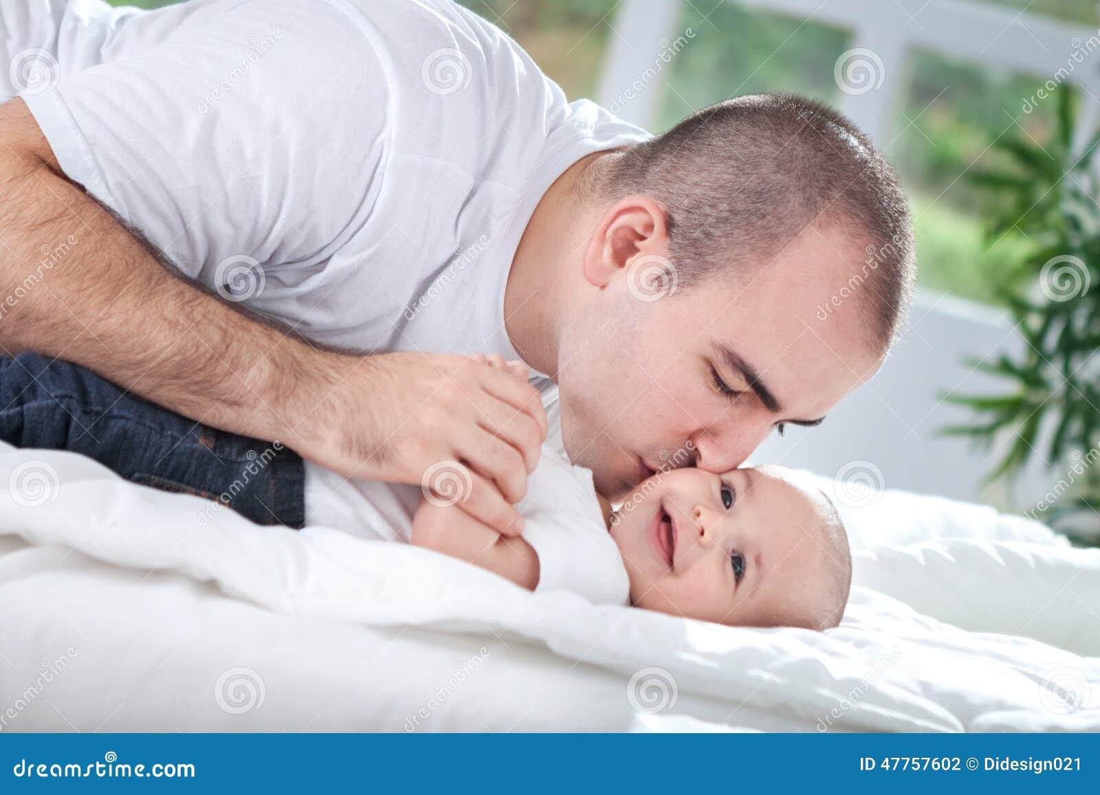 Padre joven que da un beso a su bebé