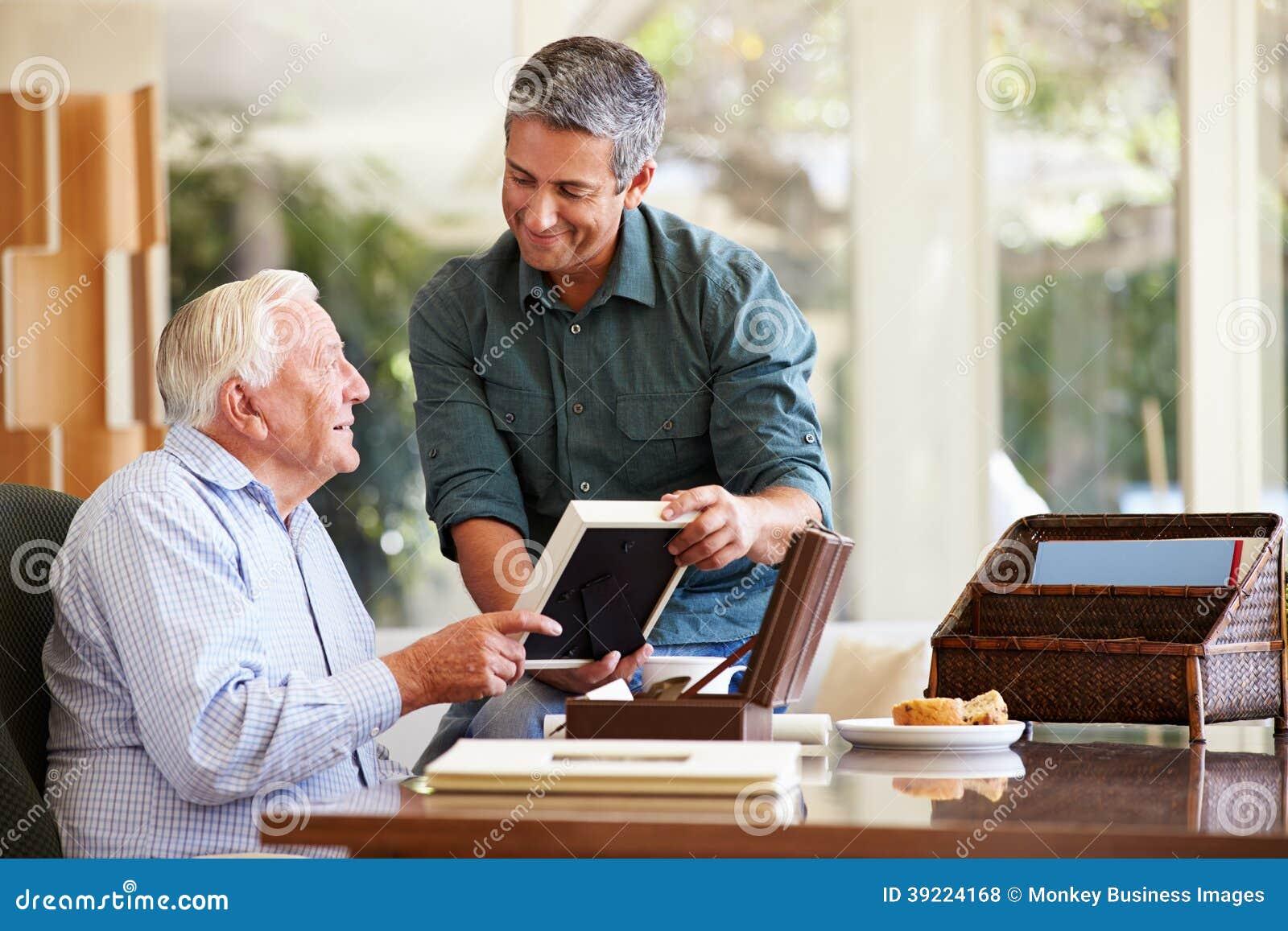 Padre mayor Looking At Photo en marco con el hijo adulto