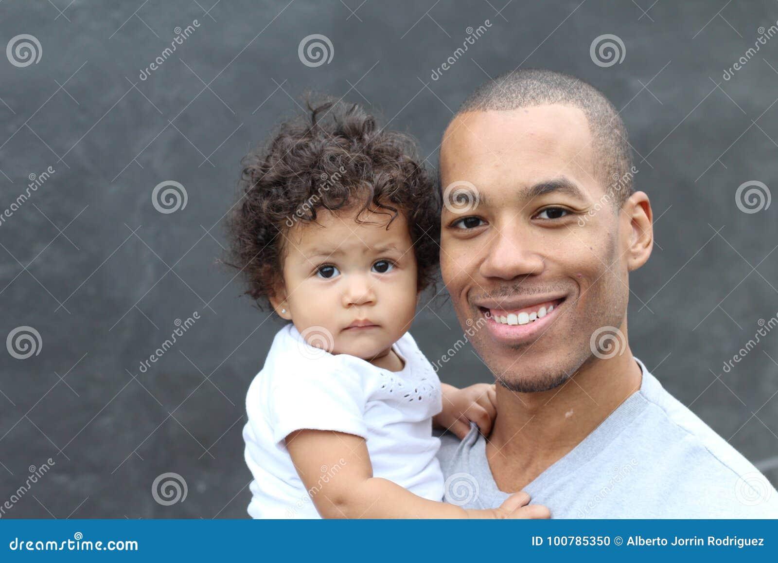 Padre nero felice e piccola figlia sveglia che abbracciano, sorridendo