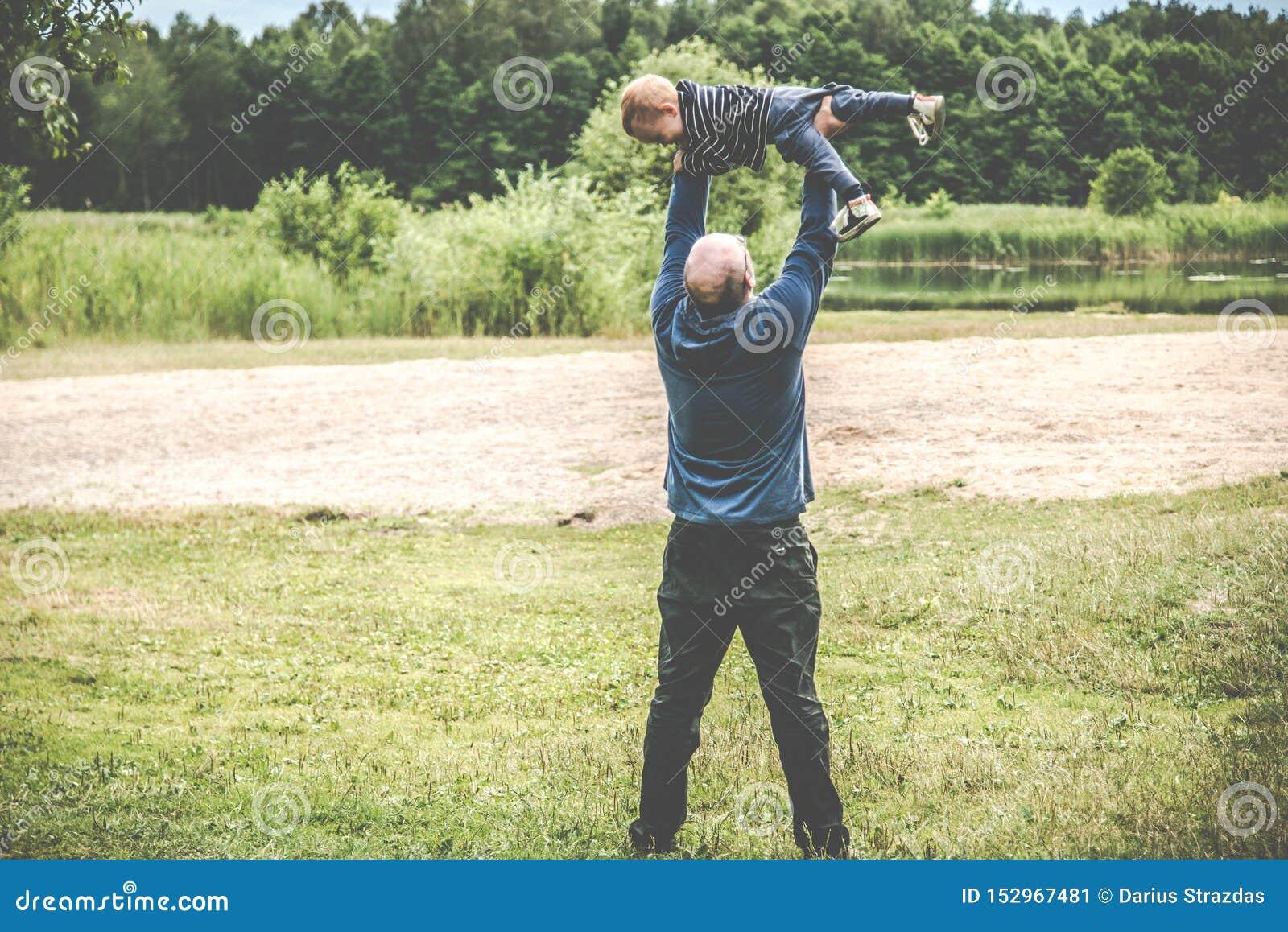 Padre que juega con su niño al aire libre, vuelo