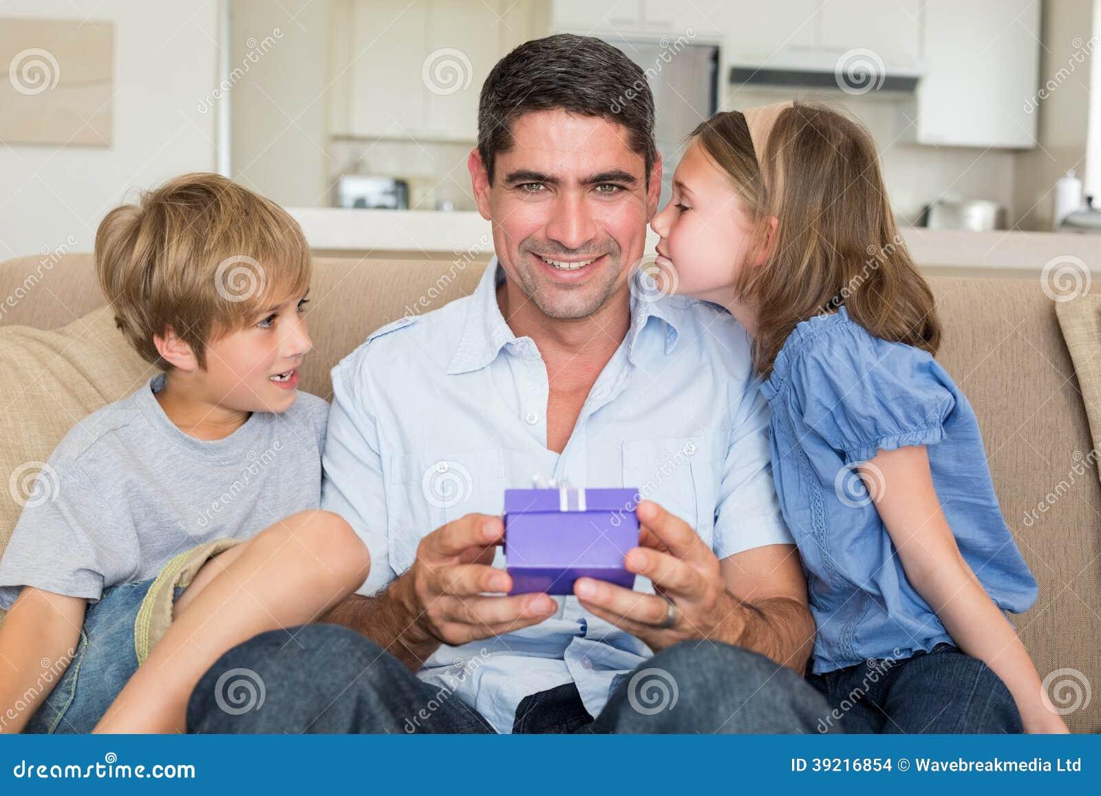 Padre que recibe el regalo de niños cariñosos