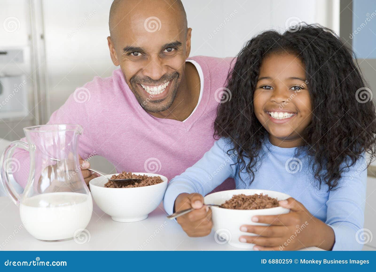 Padre que se sienta con el desayuno de Eatting de la hija