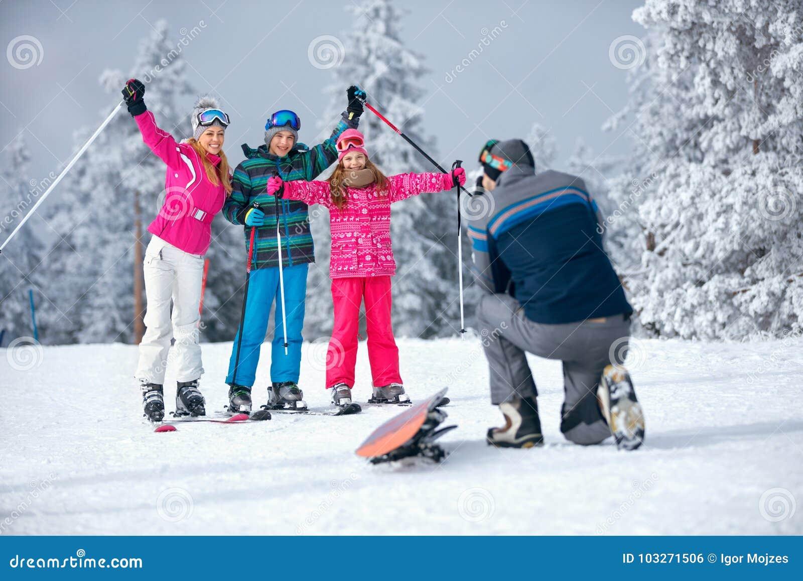 Padre que toma la imagen de la familia el día de fiesta del esquí en montañas
