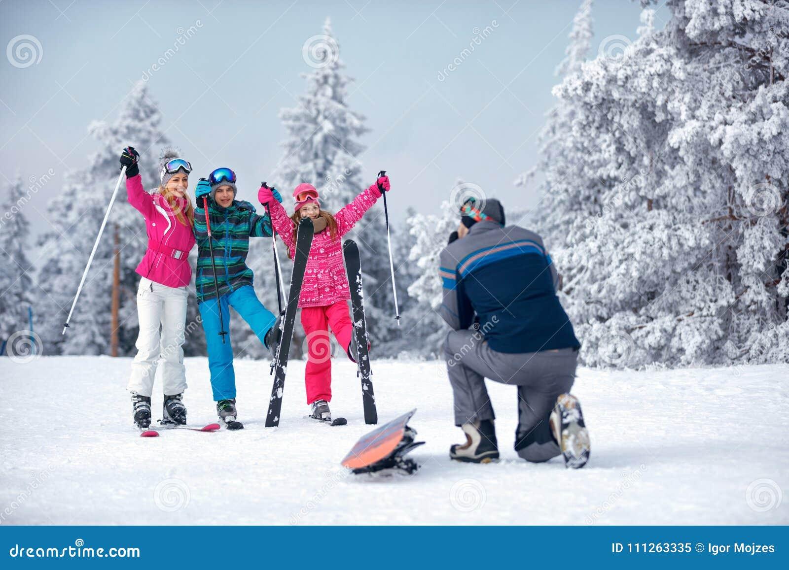 Padre que toma la imagen de la familia en snowoutdoor en día soleado