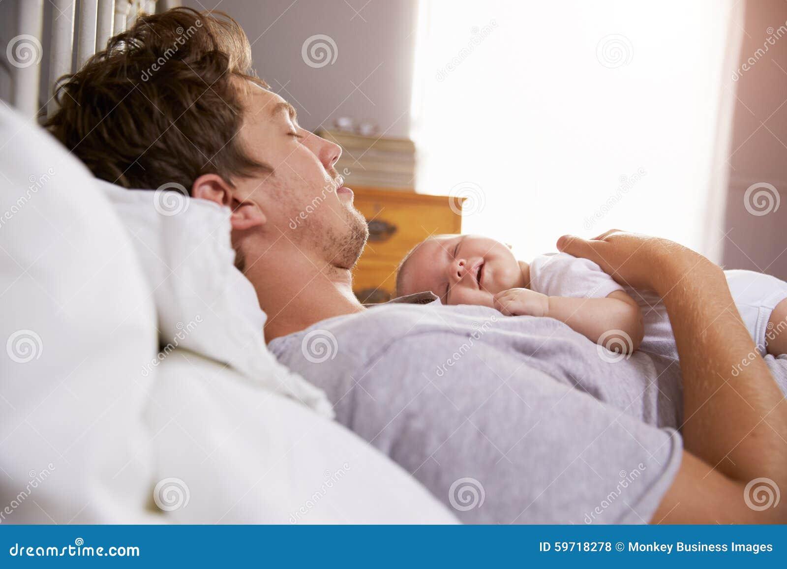 Padre Sleeping In Bed que detiene a la hija recién nacida del bebé