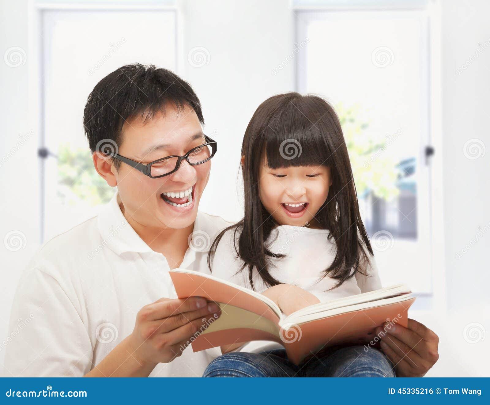 Padre sorridente e sua figlia che leggono un libro