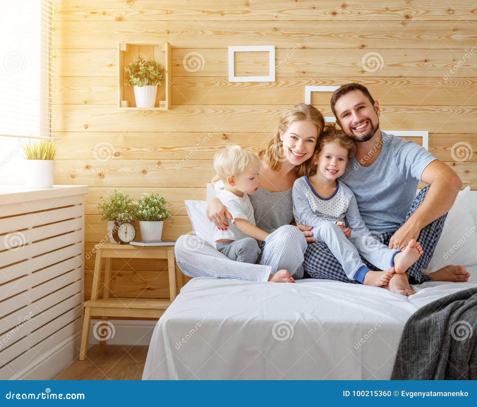 Padre y niños felices hija e hijo de la madre de la familia en cama