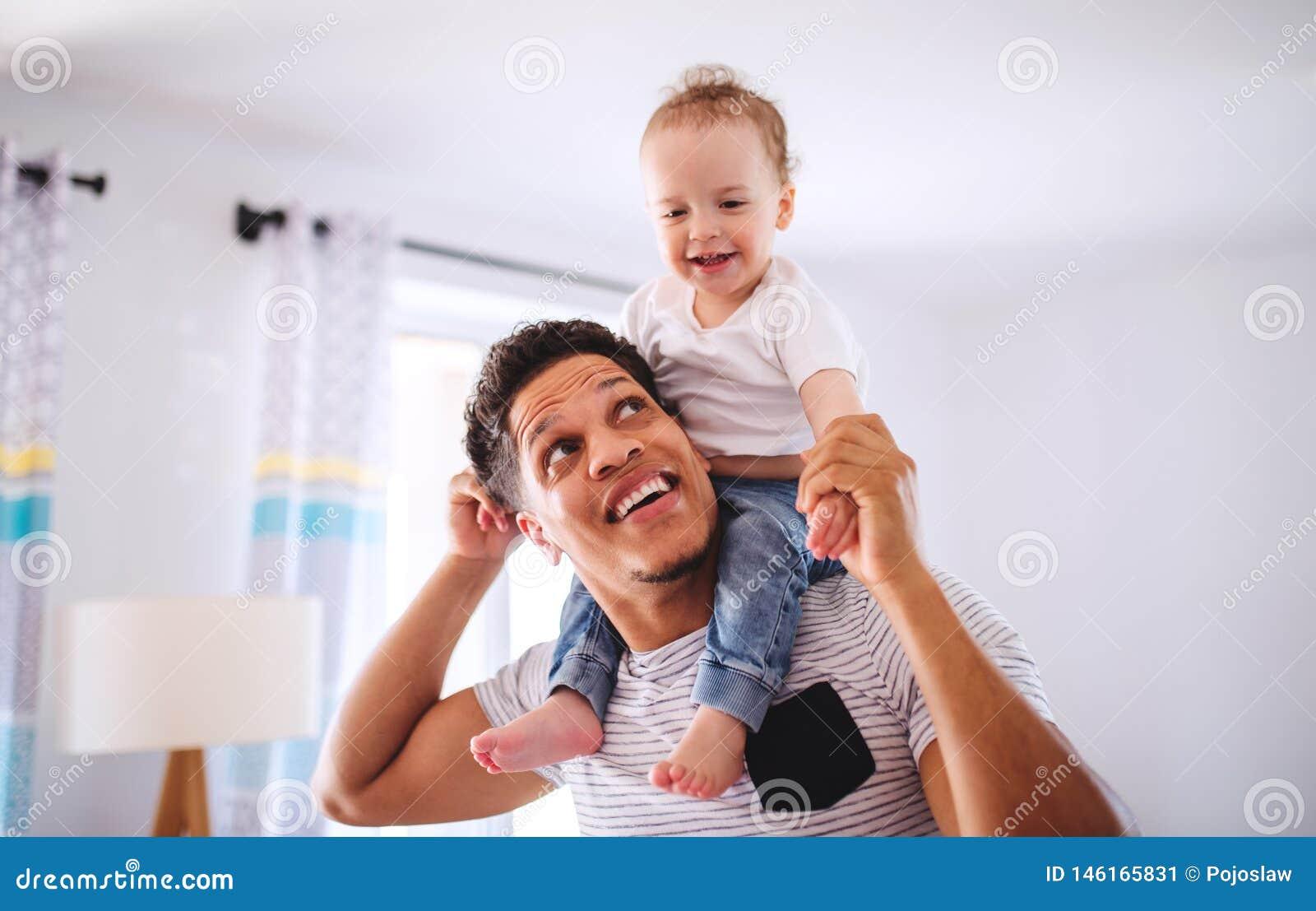 Padre y pequeño hijo del niño dentro en casa, jugando