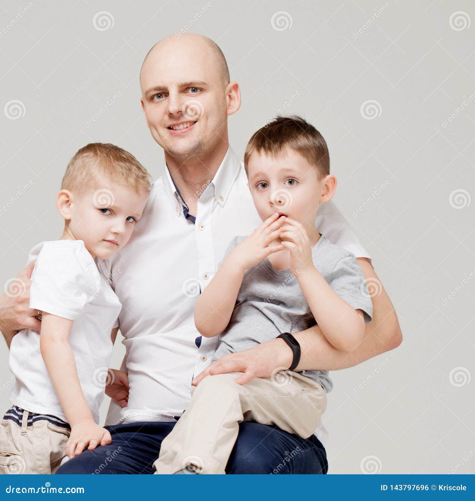 Padre y sus dos hijos, el hombre joven que cría a los niños, el retrato del concepto