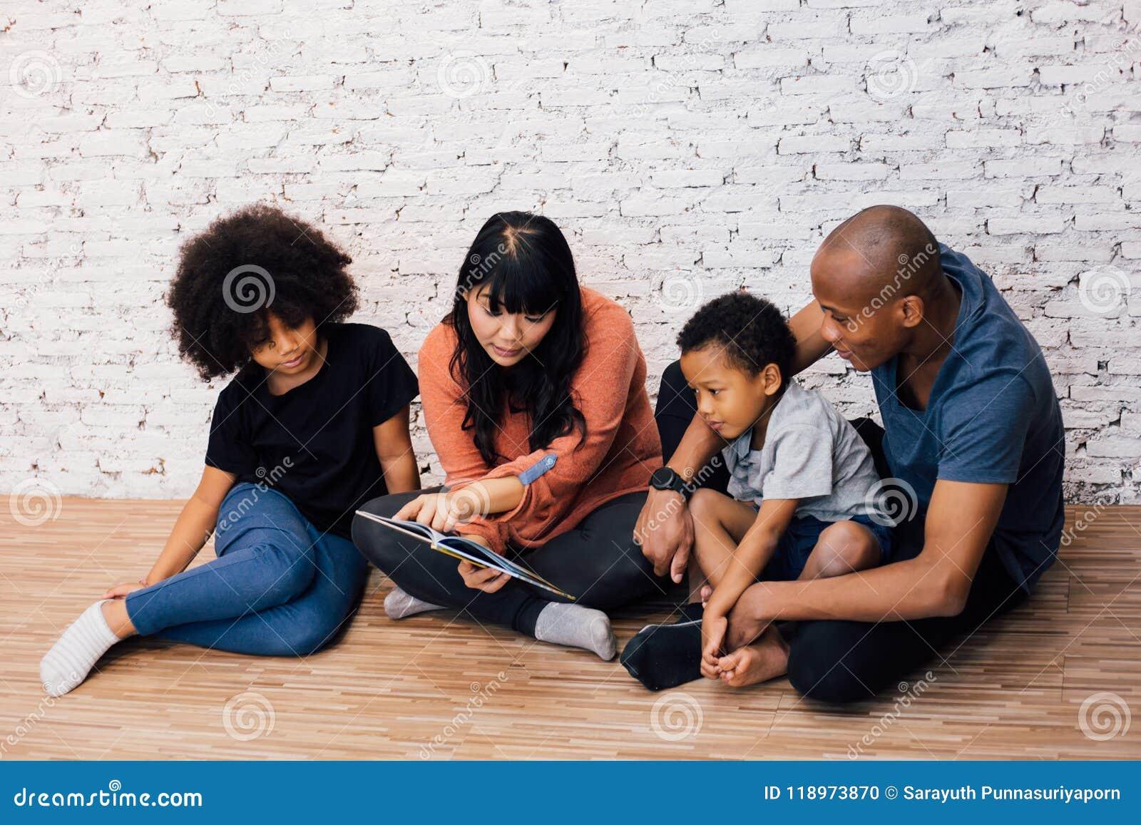 Padres afroamericanos que leen una historia de la fábula del cuento de hadas para los padres americanos kiAfrican que leen una hi