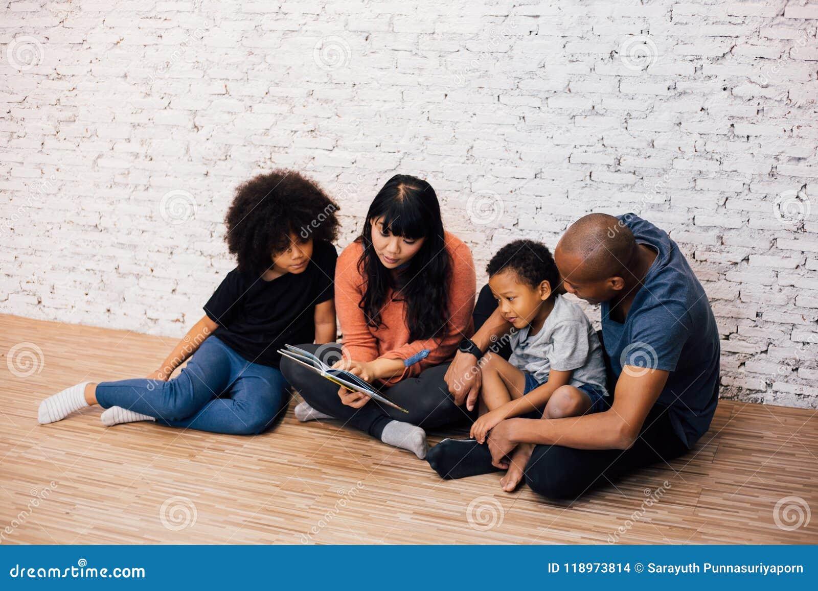 Padres afroamericanos que leen una historia de la fábula del cuento de hadas para los niños en casa Familia feliz que se sienta e