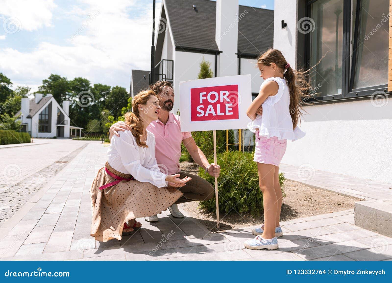 Padres agradables agradables que miran a su hija