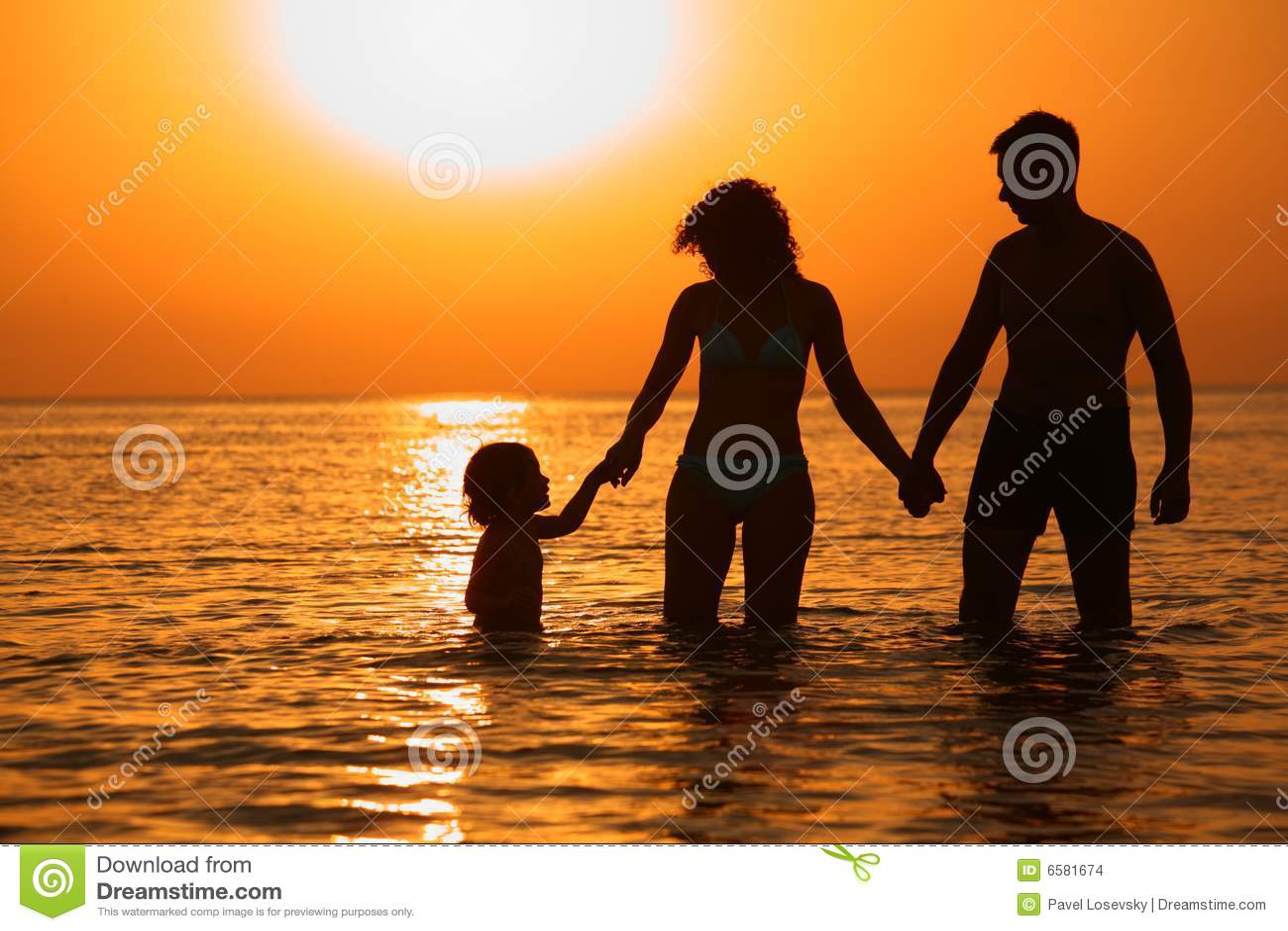 Padres con el niño en el mar en puesta del sol