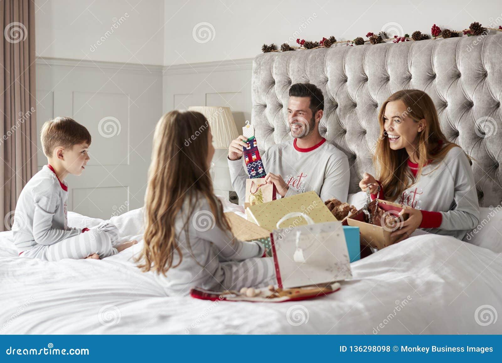 Padres que abren los regalos de niños como ellos Sit On Bed Exchanging Present el día de la Navidad
