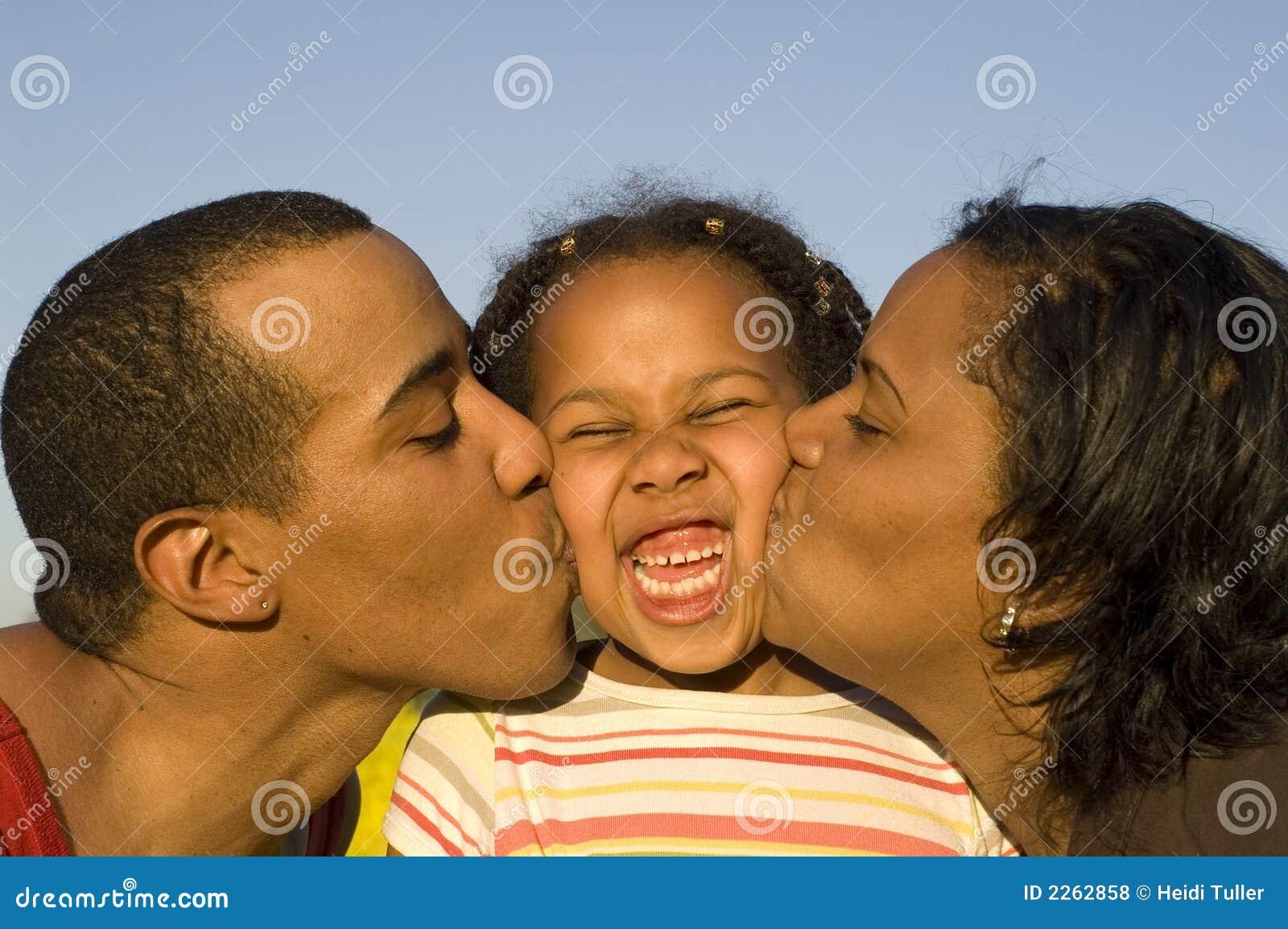 Padres que besan a la hija