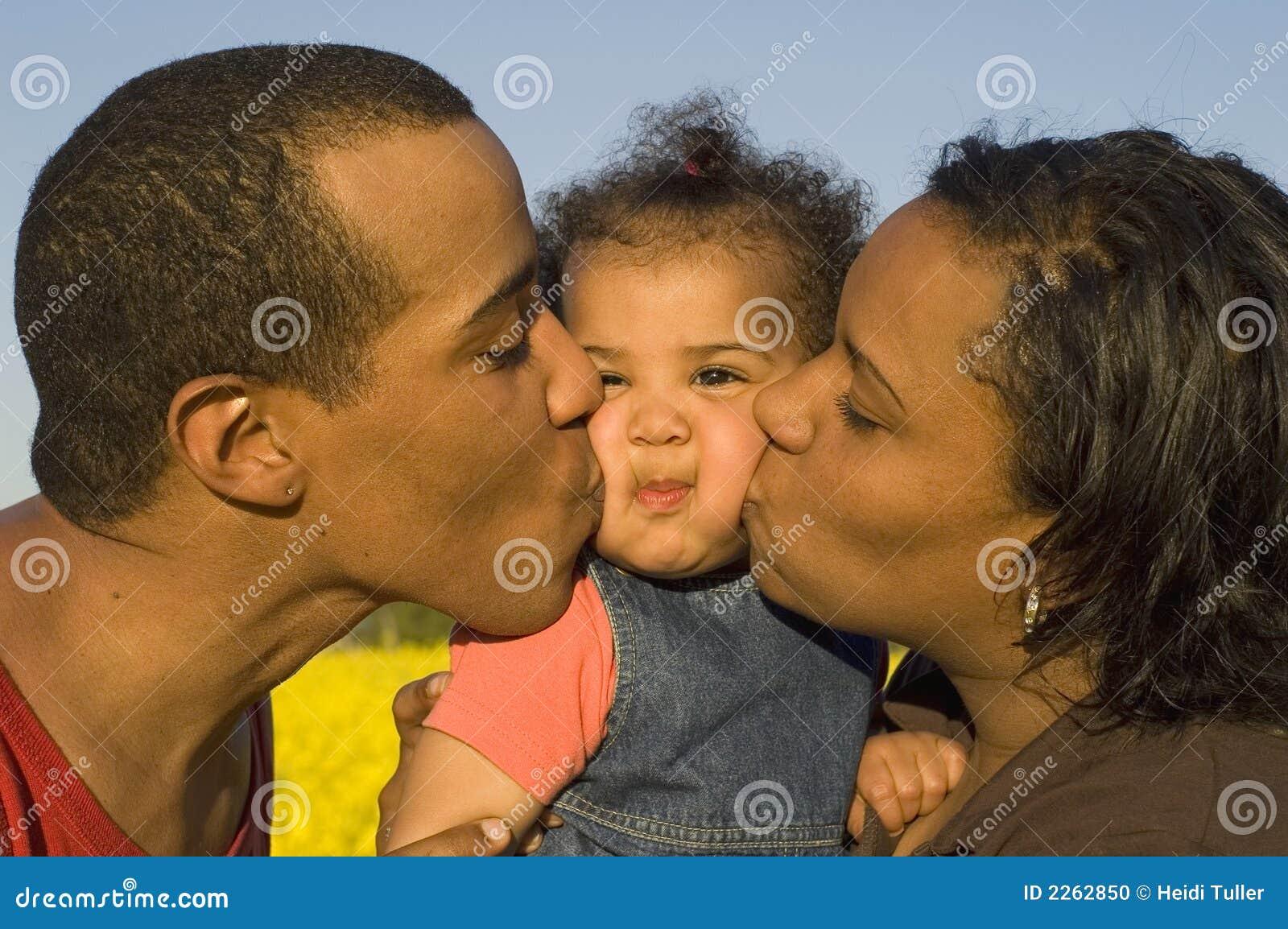 Padres que besan a su bebé