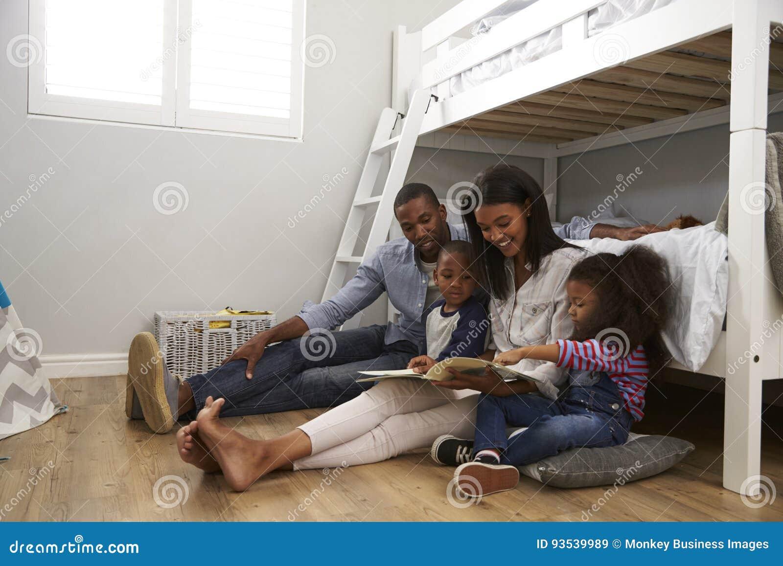 Padres que leen historia a los niños en su dormitorio