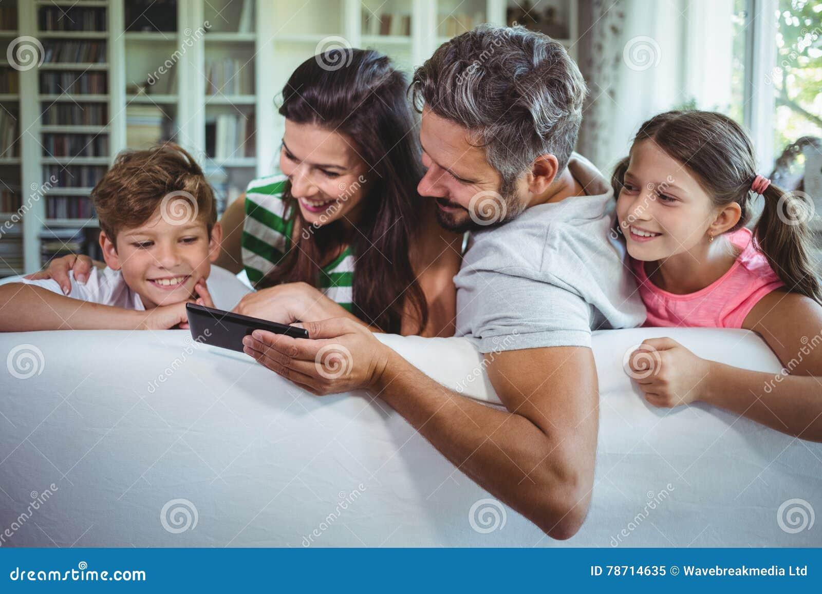 Padres que se sientan en el sofá con sus niños y que usan el teléfono móvil en sala de estar