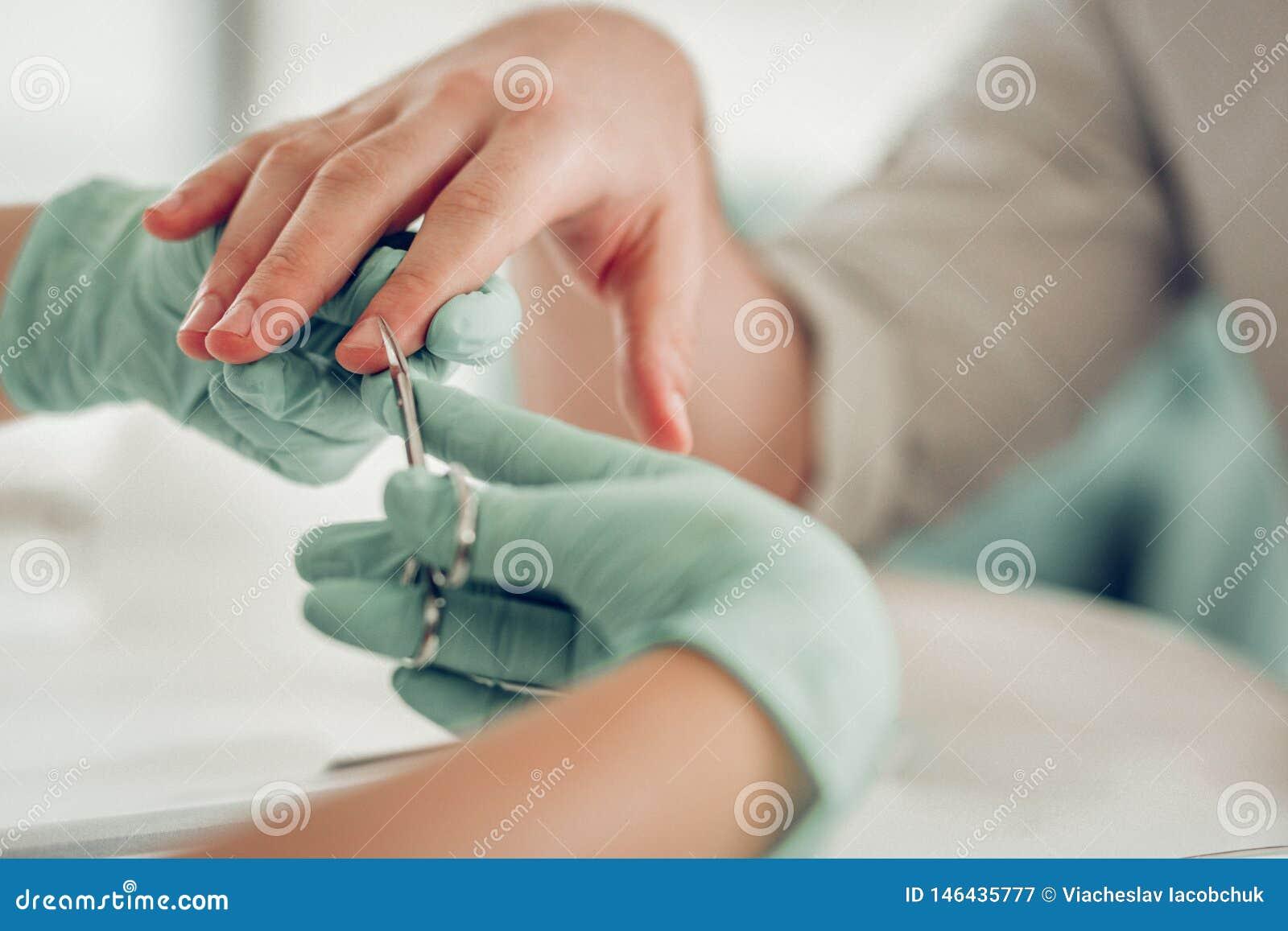 In padrone esperto accurato del chiodo in guanti di gomma protettivi che tagliano pelle extra