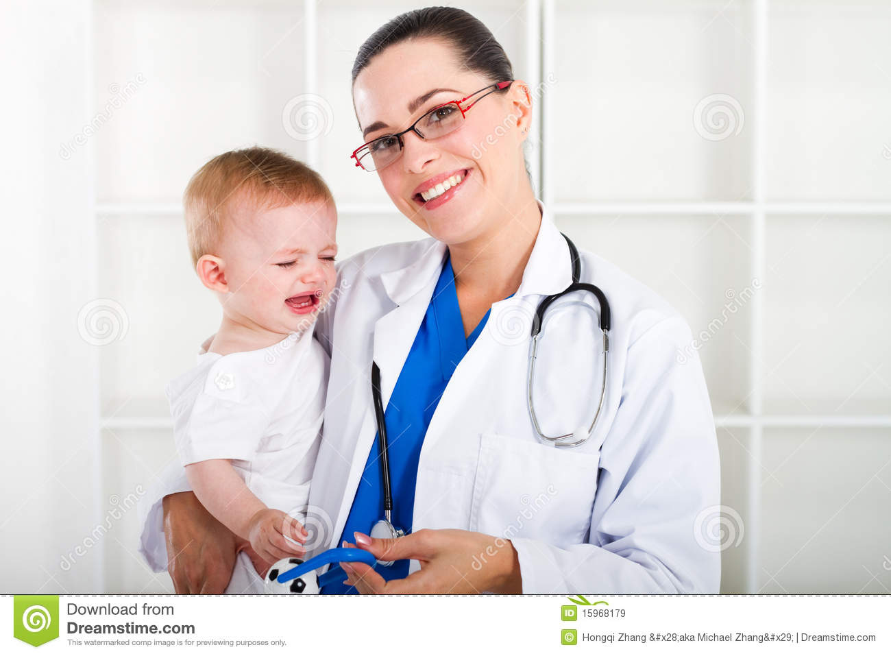 pretty young paediatrician holding a cute crying baby girl in ...