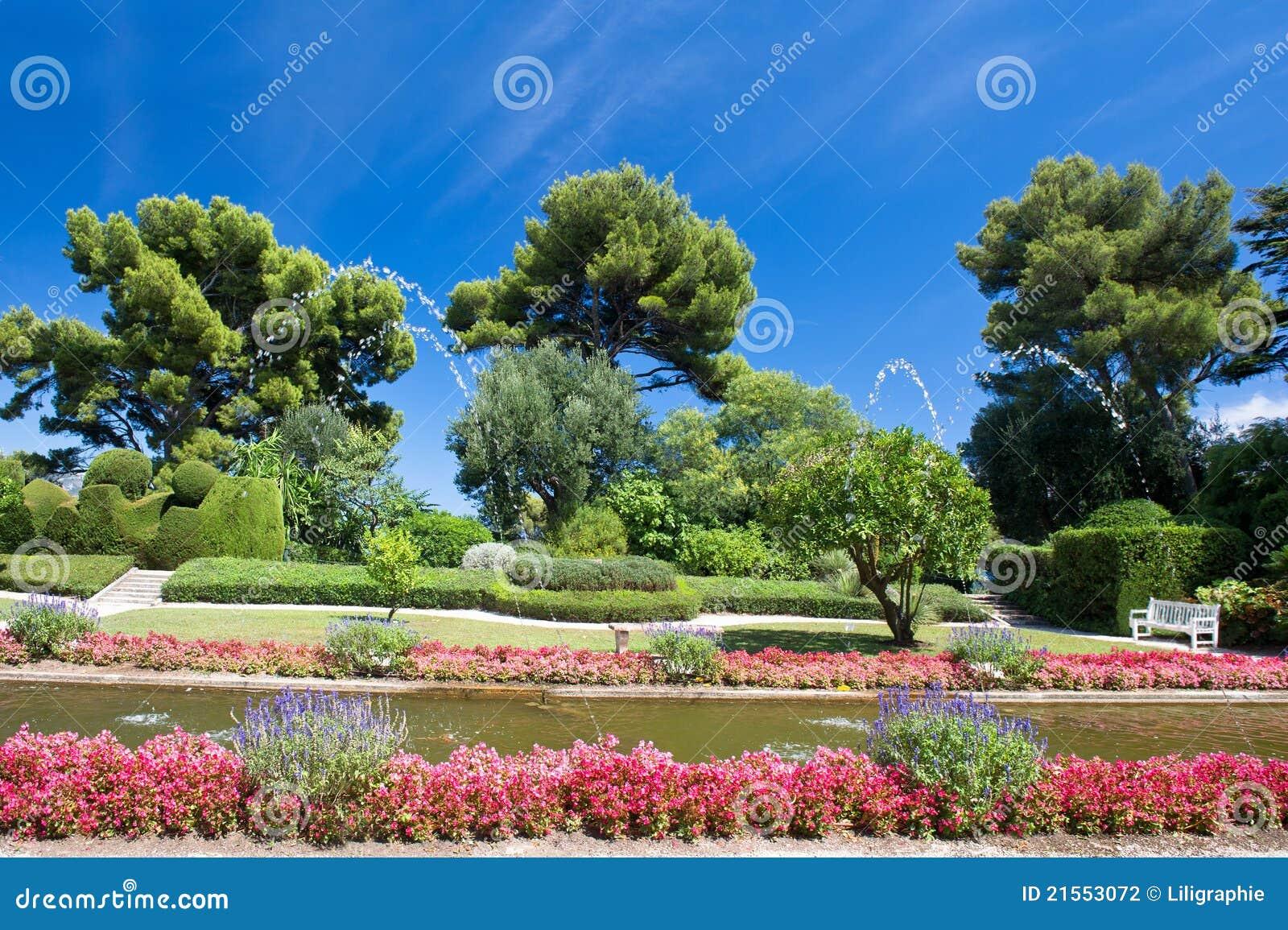 Paesaggio del giardino con i fiori variopinti ed il cielo blu perfetto