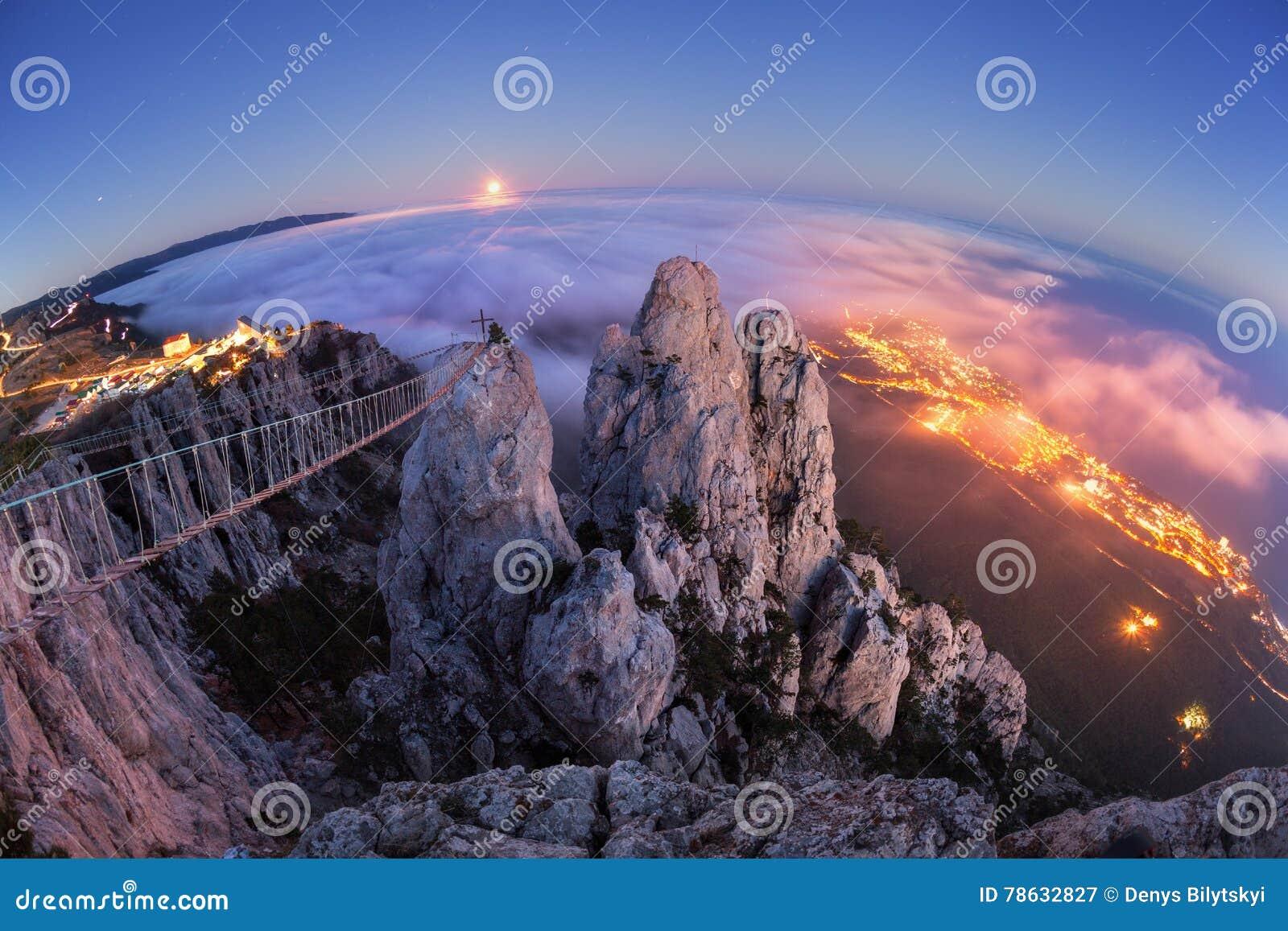 Paesaggio della montagna con la luna piena in aumento alla notte