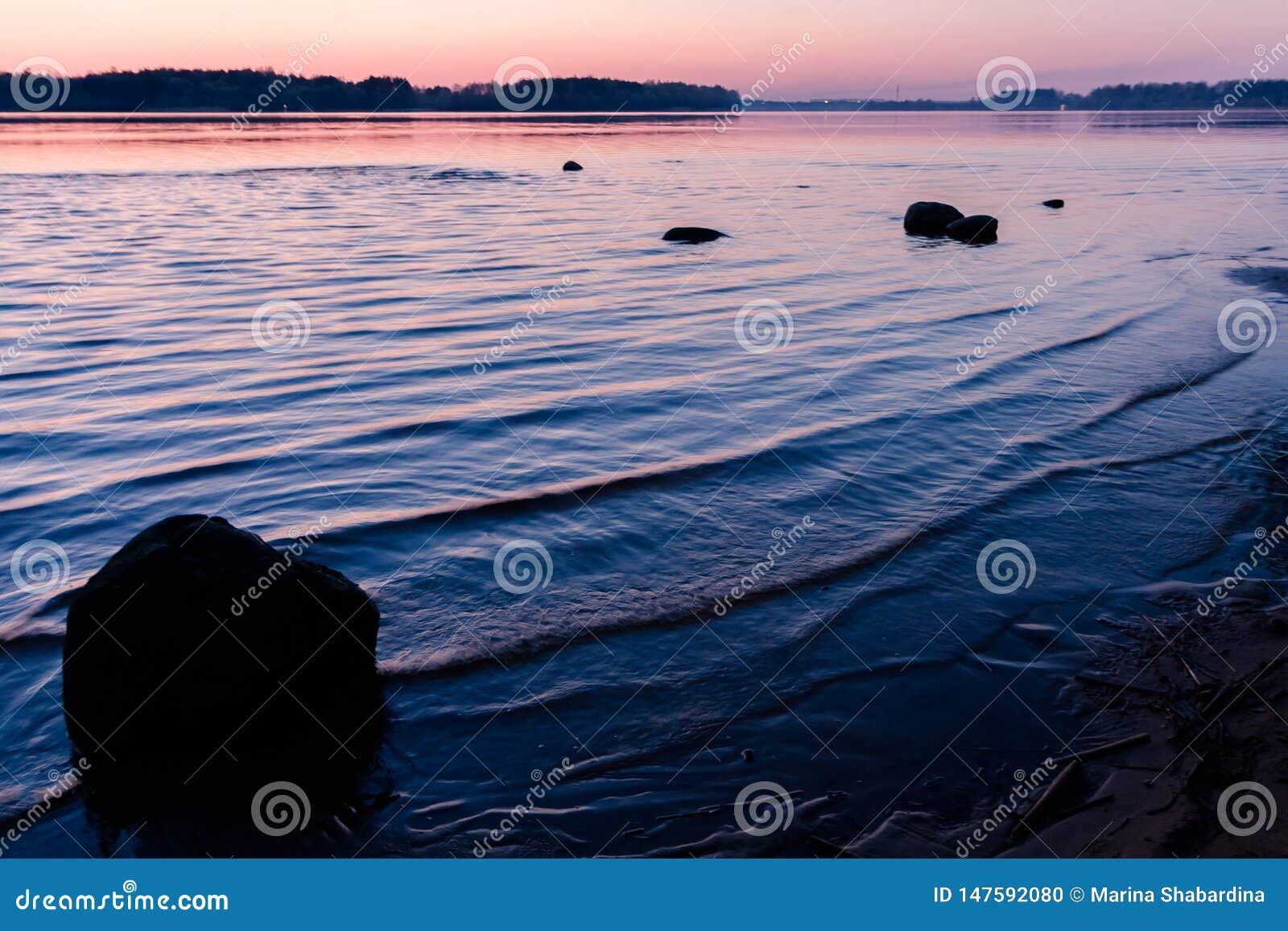 Paesaggio di rilassamento con un tramonto rosa su un fiume ondulato e sulle siluette di grandi pietre