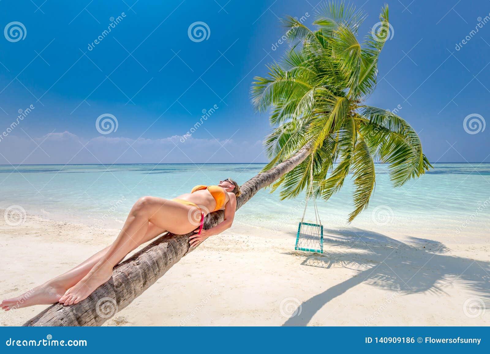 Paesaggio di stupore, palma con oscillazione sopra il mare con la donna che si rilassa sul tronco della palma, paesaggio tropical