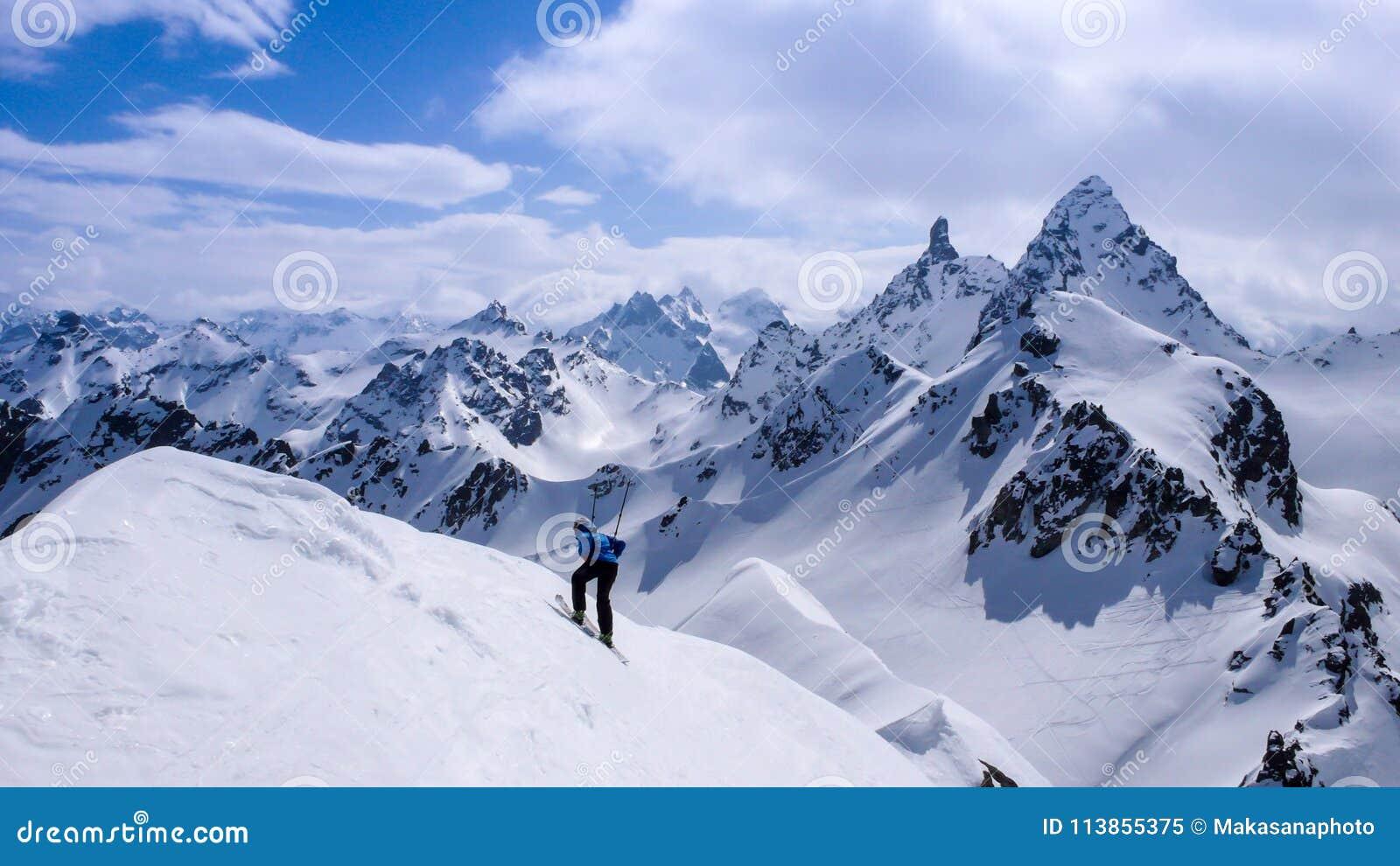 Paesaggio fantastico della montagna di inverno con uno sciatore remoto maschio nella priorità alta