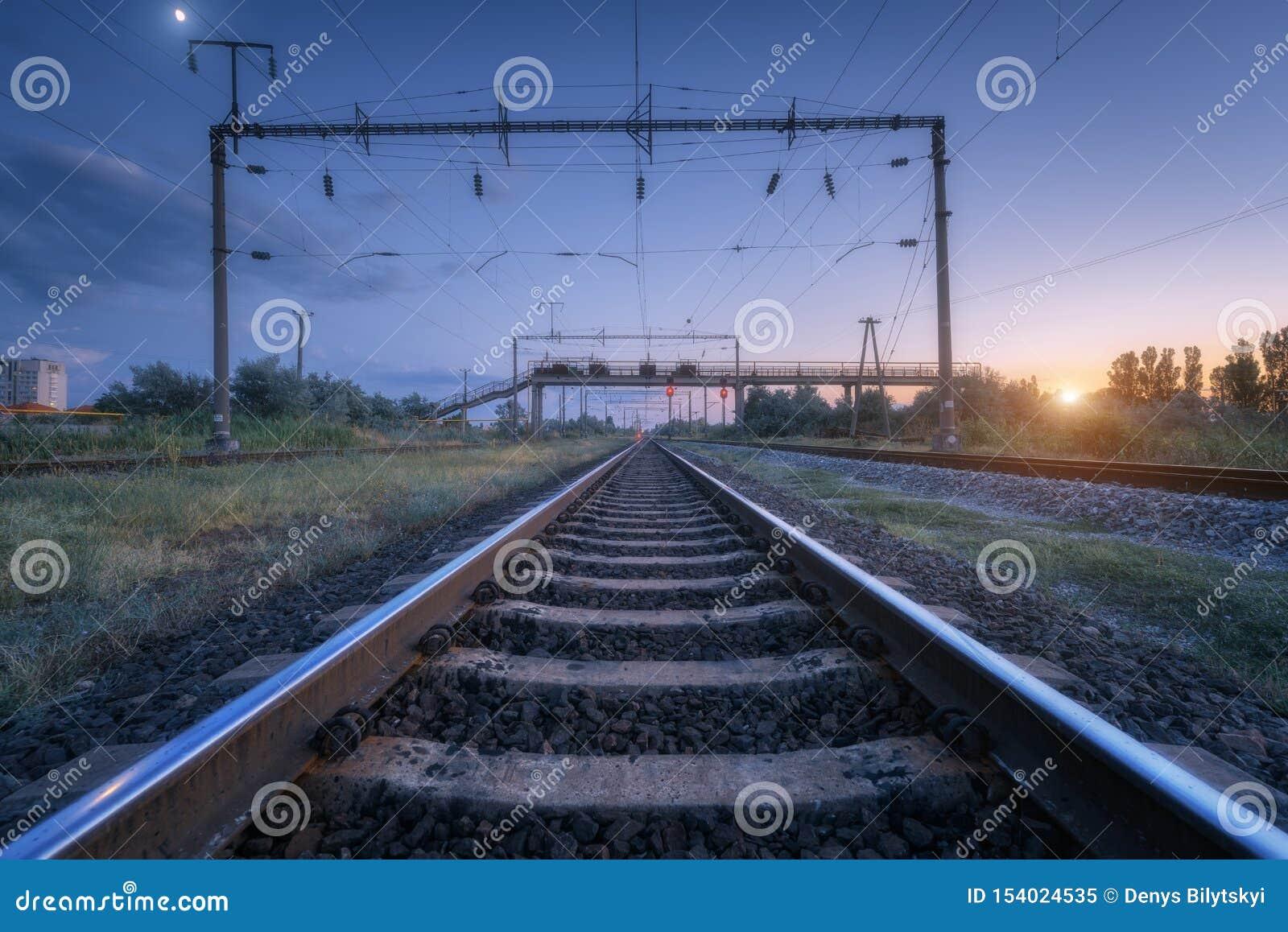 Paesaggio industriale rurale di estate con la stazione ferroviaria al tramonto