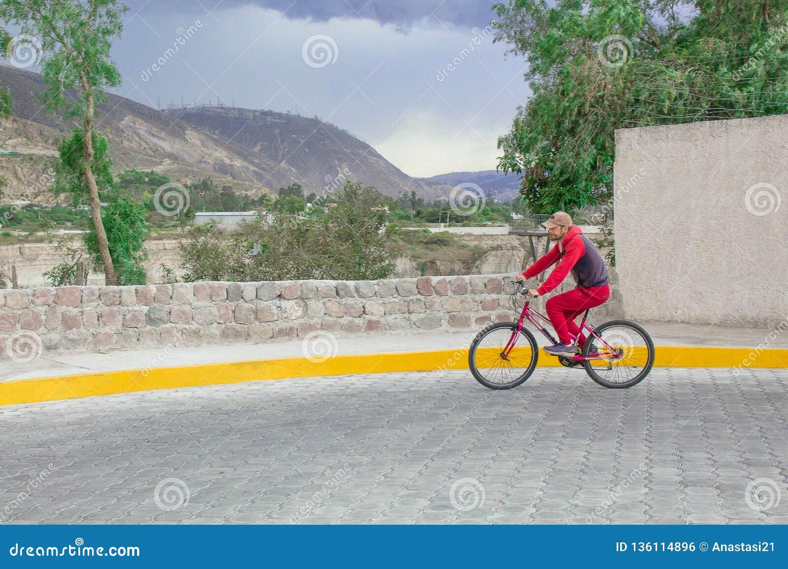 Paesaggio, montagne e natura La strada è posta con una pietra e un uomo la guida su una bicicletta, azionamenti lungo la strada