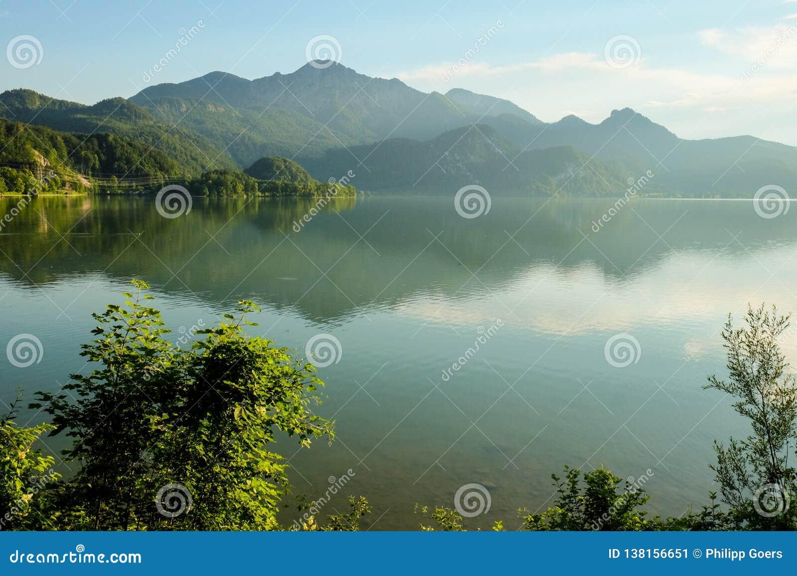 Paesaggio nebbioso idilliaco della montagna con un lago e montagne nei precedenti