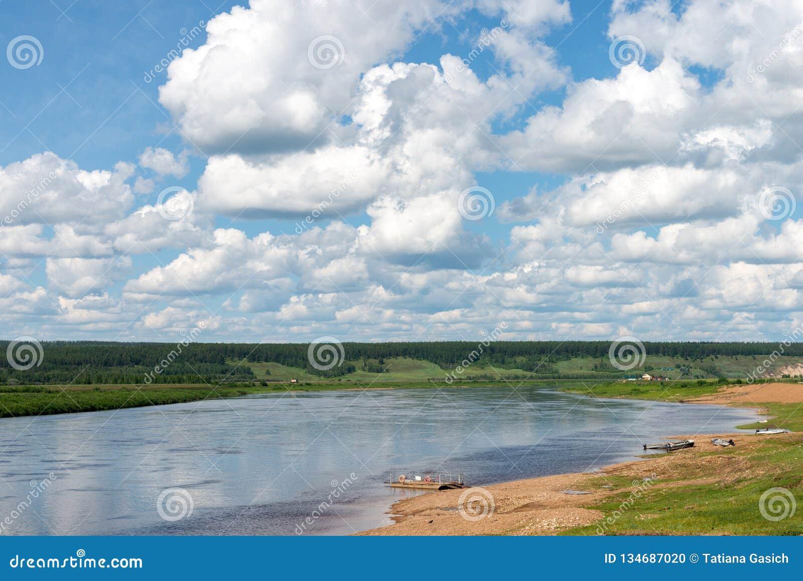 Paesaggio rurale con il villaggio ed il fiume al giorno nuvoloso di estate